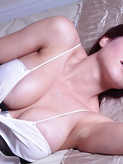 Amber Bambi strips naked on her bed from her top and tight shorts