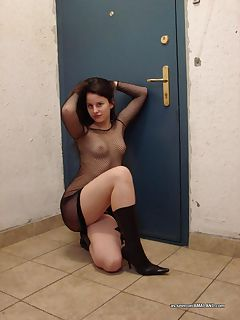 Photo gallery of a sexy shaven brunette MILF in fishnet lingerie and boots