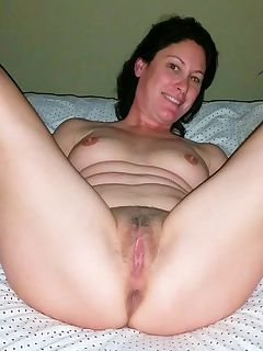 Naked housewife likes posing naughty on the bed while spreading her cunt