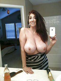 Fantastic busty MILF taking pic of her perfect boobs in bathroom mirror